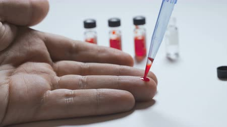 doação : Doctor taking blood sample from male hand at lab.
