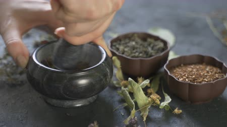 bewitch : Preparation of medicinal herbs for use. Medicinal plants on the table. Woman rubs medicinal plants in a mortar