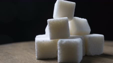 sweetener : A pile of sugar pieces rotates against a black background
