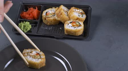 california rolls : a woman takes a roll using wooden chopstick. Close-up. Traditional Japanese cuisine.