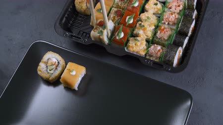 servido : Woman puts sushi rolls on the plate. A large set of rolls is on the table. Japanese food