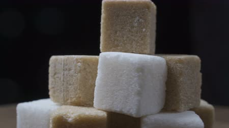 cukorbaj : cubes of white and cane sugar rotate on a black background