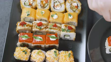 plating food : Close up of chopsticks holds sushi maki gunkan roll over a plate or platter set. Served in Japanese bar restaurant. Top view, flat lay. Food background. copy space