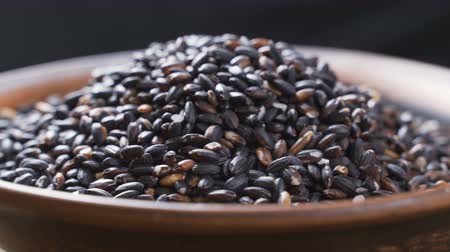 nutricional : Grains of black rice spinning on a clay plate