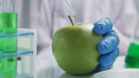 engineered : Food science researchers working in laboratory, 1 woman injecting chemicals into apple Stock Footage