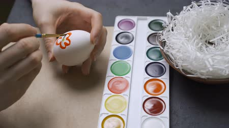fingers : A family paints and decorates easter eggs at the table