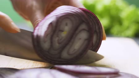 tábua de cortar : Cutting red onion on wooden board. Woman hand cutting red onion on the table Stock Footage