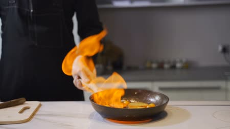 환대 : Chef frying food in flaming pan on gas hob in commercial kitchen.