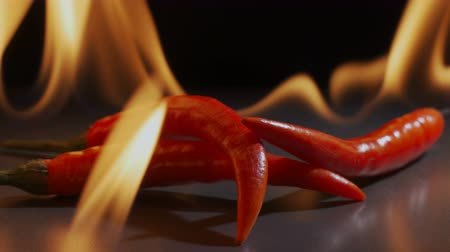 condimentos : three red peppers lie in a flame on a dark background