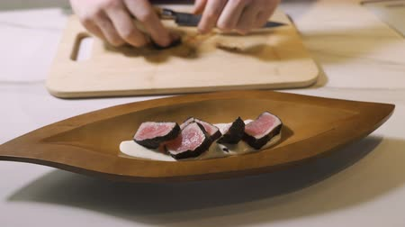 seafood recipe : Hands put sushi on plate. Long plate with sushi rolls. Japanese chef gives master class. Stock Footage