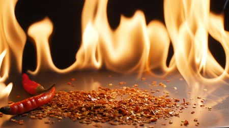 calabresa : Red chili falling down with flames in the background in slow motion
