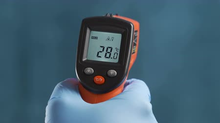 диагностировать : The scientist measures the temperature using a remote infrared pyrometer