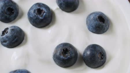 yoğunluk : Eating blueberries with cream or yogurt by spoon, fruit background. Stok Video