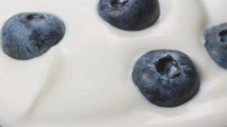 desszertek : Eating blueberries with cream or yogurt by spoon, fruit background. Stock mozgókép