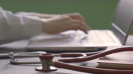 Doctor is typing text on laptop. Stethoscope on medical documents Стоковые видеозаписи
