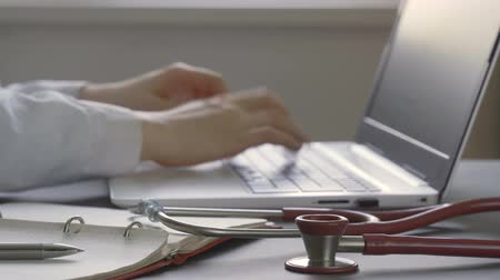 documents : Doctor is typing text on laptop. Stethoscope on medical documents Stock Footage