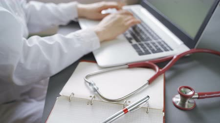 telemedicine : Telemedicine concept. Doctor working with laptop and diagnosis form in a front Stock Footage