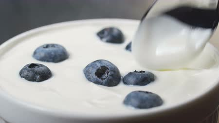bilberry : Eating blueberries with cream or yogurt by spoon, fruit background. Stock Footage