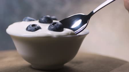 kalcium : Slow motion young female hand eating blueberry yogurt with spoon