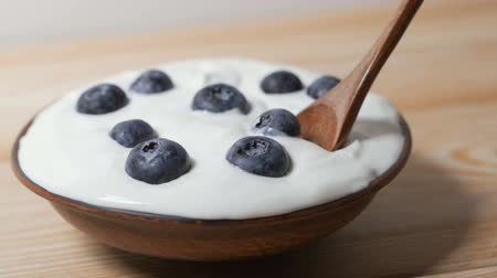 Eating blueberries with cream or yogurt, by spoon.