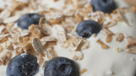 owies : Composition of a typical genuine breakfast made with yogurt, blueberries, muesli.
