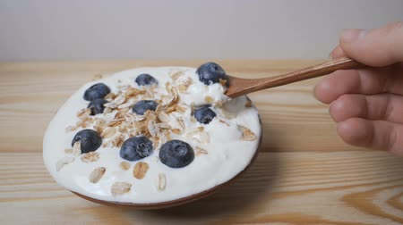 Eating blueberries with cream or yogurt and muesli, by spoon. Стоковые видеозаписи