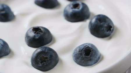 Closeup Blueberries in natural yogurt rotating. 4k. Fruit background.