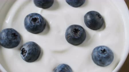 Blueberries in organic yogurt rotating loop video, 4k footage