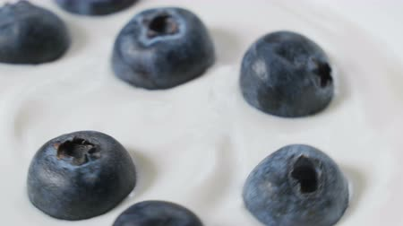 Eating blueberries with cream or yogurt by spoon, fruit background. Стоковые видеозаписи