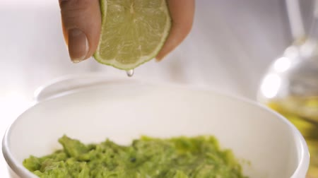 woman cooks guacomole and squeezes fresh lime