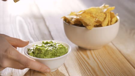 kolendra : People dipping corn chips into guacamole dip