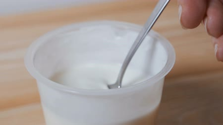 yoghurt : The girl eats yogurt from a jar.