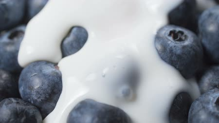 Blueberries in organic yogurt. Yogurt pours blueberries. Close-up