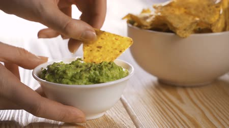 Person eating guacamole while scooping a chip Стоковые видеозаписи