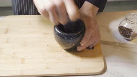 Chefs hands using a stone mortar and pestle to confidently grind a selection of herbs and spices