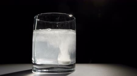 oldódó : A man throws an effervescent tablet into a glass of water.