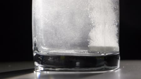aspirin tablet in glass of water over black Stock Footage