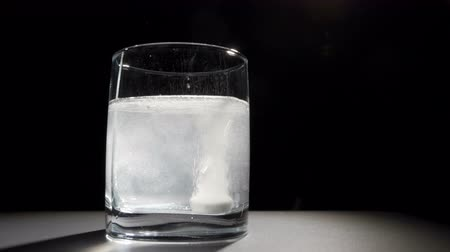 Effervescent Tablet in Glass of Water on Black