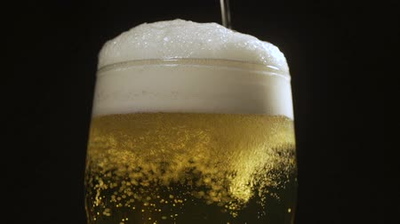 Close up background of pouring beer with bubbles and foam in glass