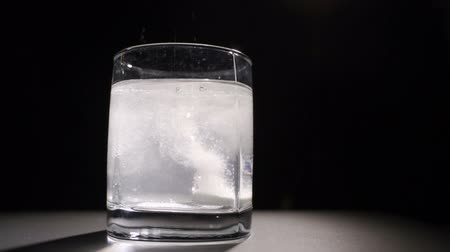 Effervescent tablet is dissolved in a glass of hot water. Dark background Stock Footage