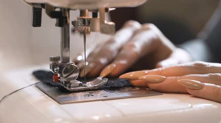Tailor sews lingerie on a sewing machine