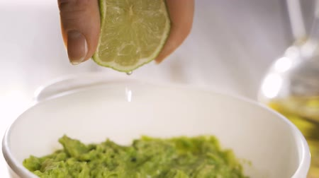 Squeezes fresh lime into a bowl of guacamole.