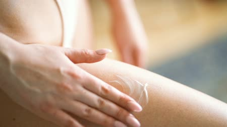 krem : Woman applying anti-cellulite cream on her thigh Stok Video