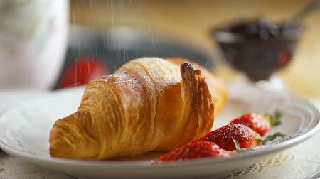 континентальный : Croissant with jam served on the table. Added strawberries and powdered sugar. Стоковые видеозаписи