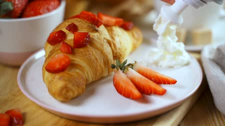 обедающий : Croissant with fresh strawberries served on the table. Waiter adds whipped cream