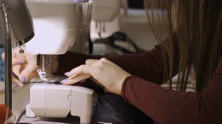 rode draad : A seamstress woman works for a sewing machine, a seamstress works on a sewing machine Stockvideo