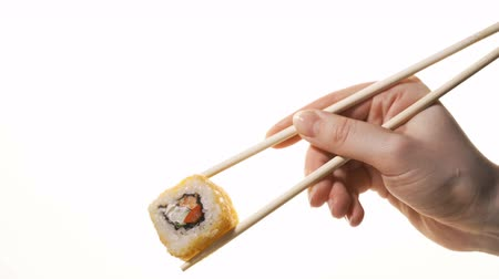нори : Hand holding Fresh sushi salmon by chopsticks isolated on white background