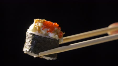нори : Girl takes chopsticks sushi on a black mirror surface, close-up. Close-up of sushi rolls with chopsticks on dark background