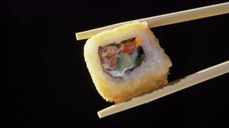 икра : Sushi in chopsticks on black background Стоковые видеозаписи
