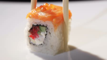 lunchen : Chopsticks Taking Sushi in a Japanese Restaurant. Close-up. Stylish white plate with Sushi